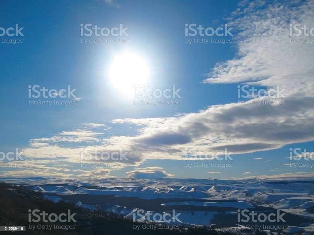 Caucasus mountains under big sun and clouds stock photo