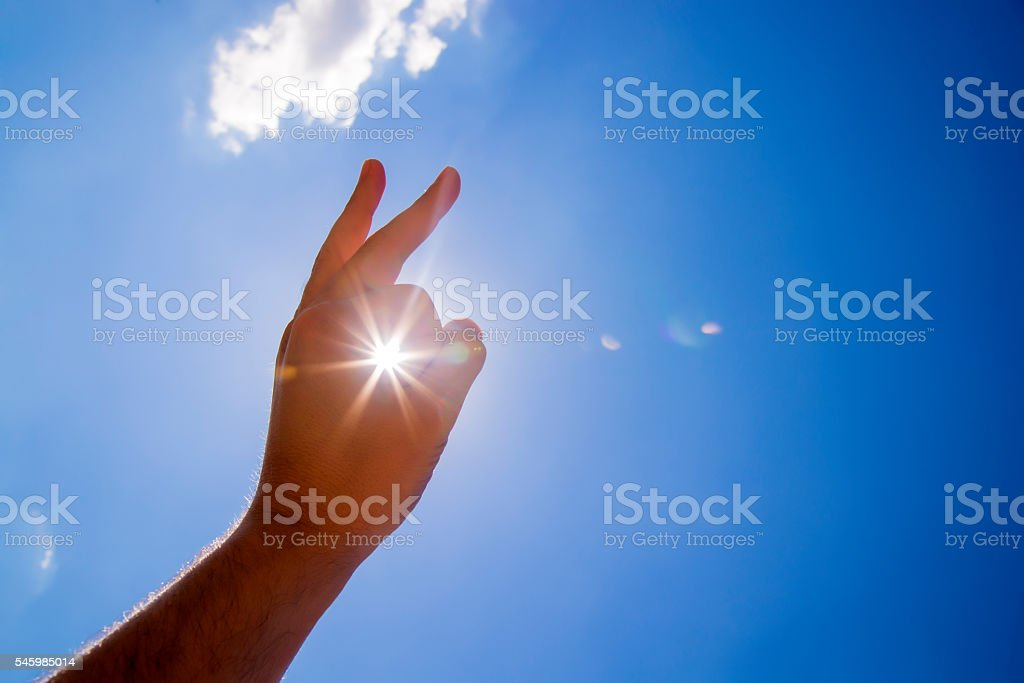 Caught the sun , Touching the Sun, Sun in hand. stock photo