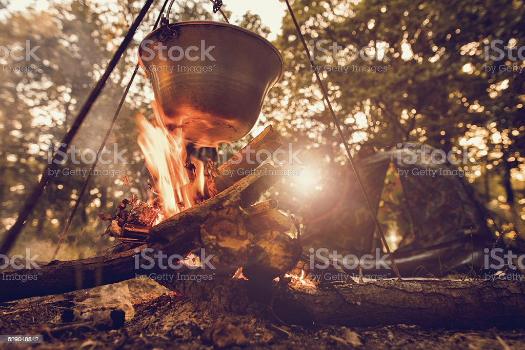 Cauldron on log fire with tent in the background. stock photo