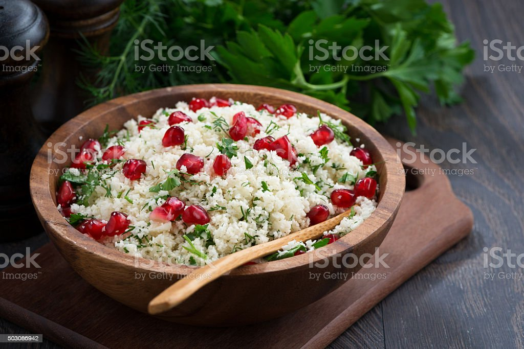 Cauliflower couscous with herbs and pomegranate on wooden table stock photo