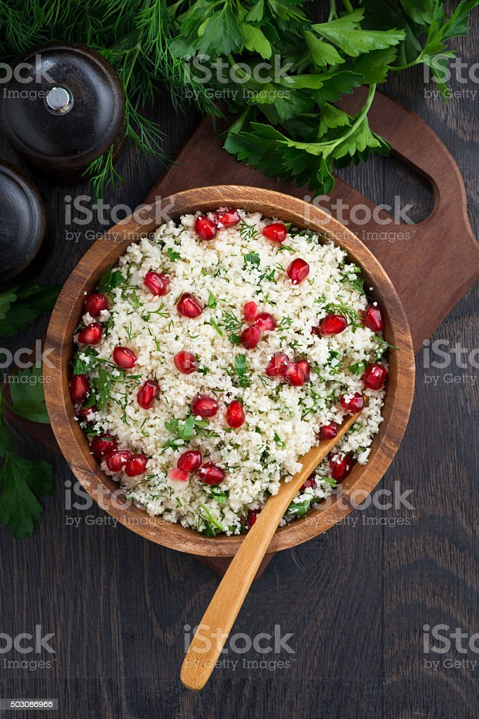 Cauliflower couscous with herbs and pomegranate, top view stock photo