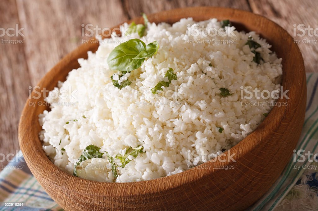 Cauliflower rice with basil in a bowl close-up. horizontal stock photo