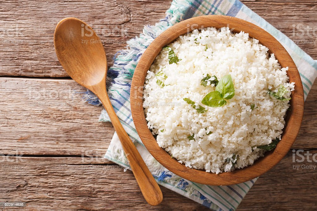 Cauliflower rice with basil in bowl close-up. Horizontal top view stock photo