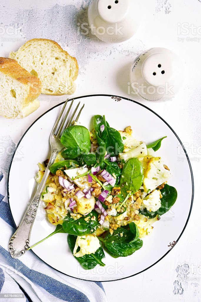Cauliflower salad with baby spinach,walnuts and red onion.Top view. stock photo