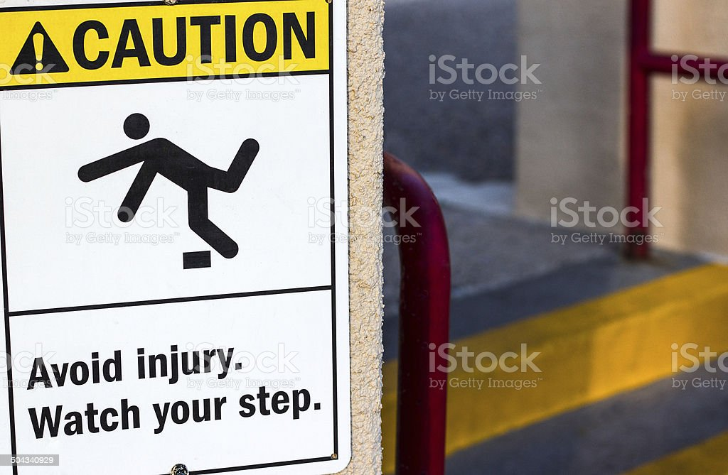 'Caution Avoid Injury' Sign with Steps in Background stock photo