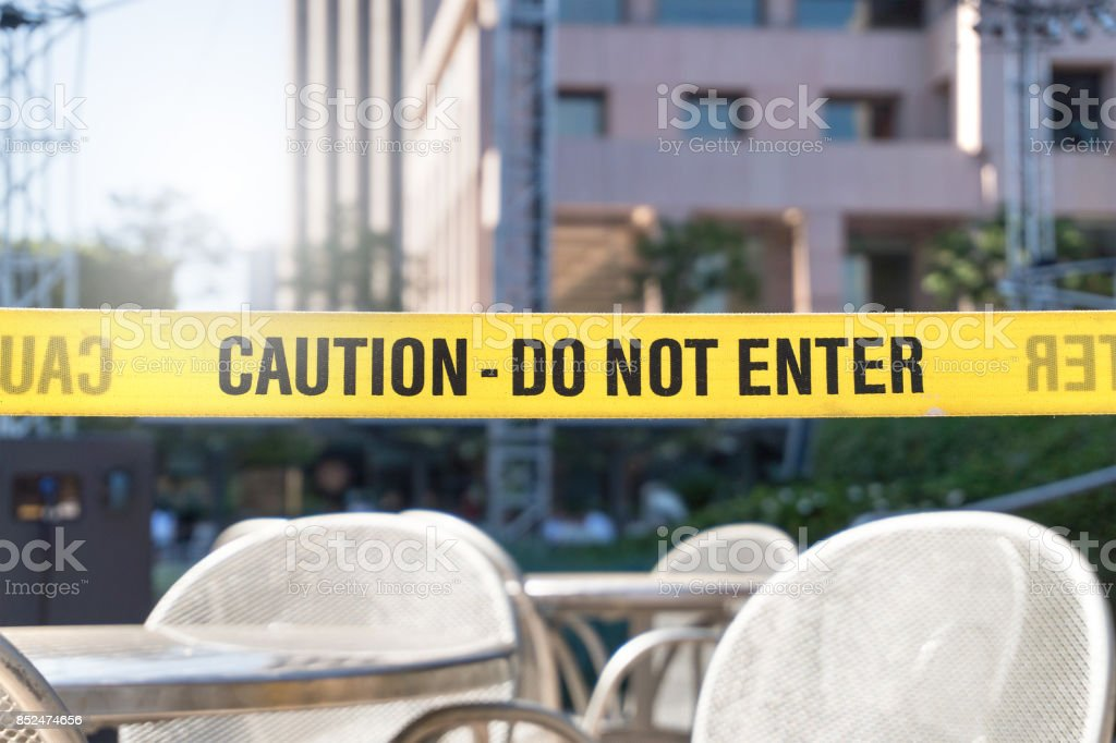 Caution, do not enter line tape and ribbon in city, outdoor terrace, restaurant or building. Construction or crime scene with a warning text. Forbidden, prohibited or restricted area. stock photo