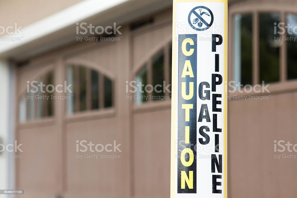 Caution gas pipeline sign near a home garage stock photo