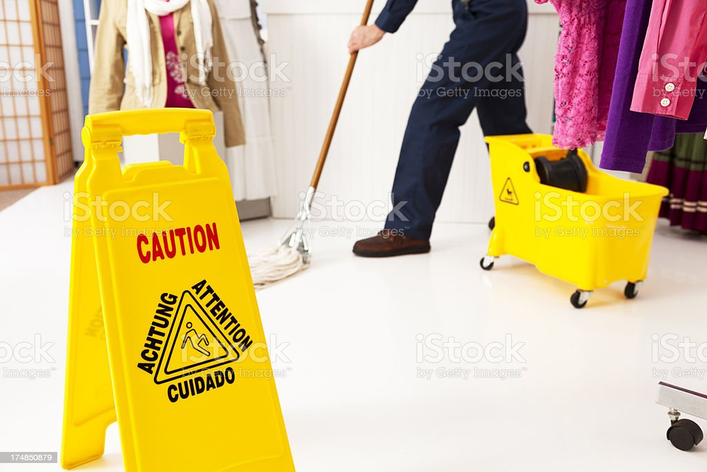 Caution sign and man mopping floor of boutique clothing store. royalty-free stock photo