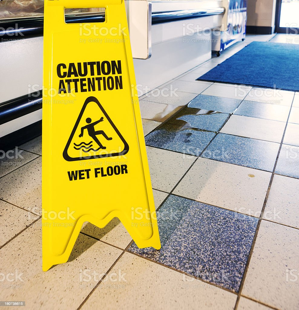 A caution sign beside a spill in a store.