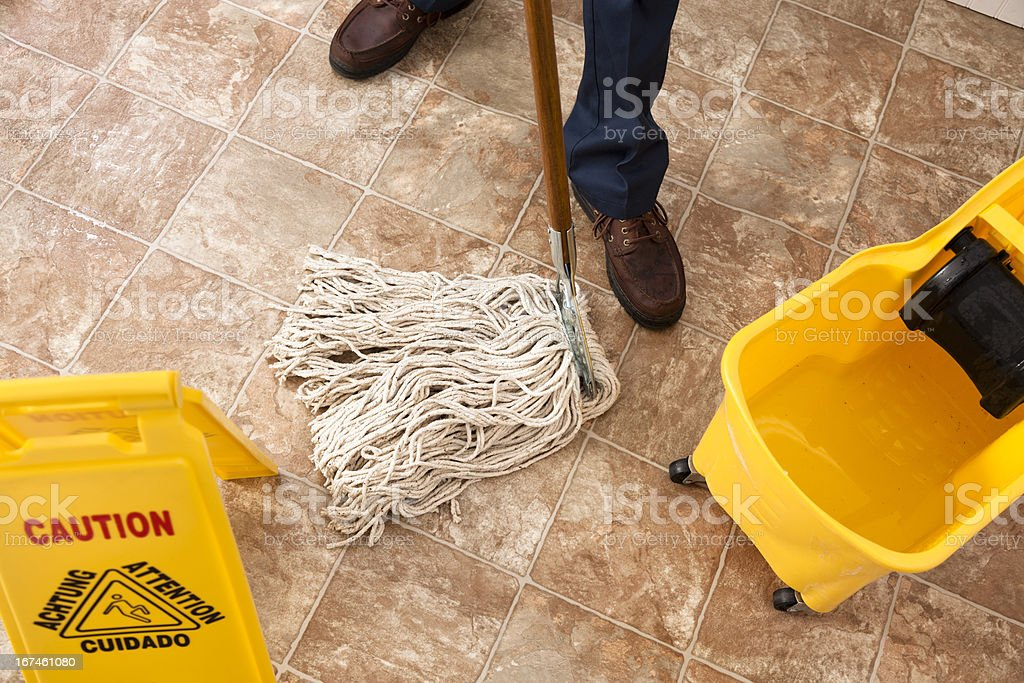 Caution sign, janitor man mopping floor of retail store. Cleaning. stock photo