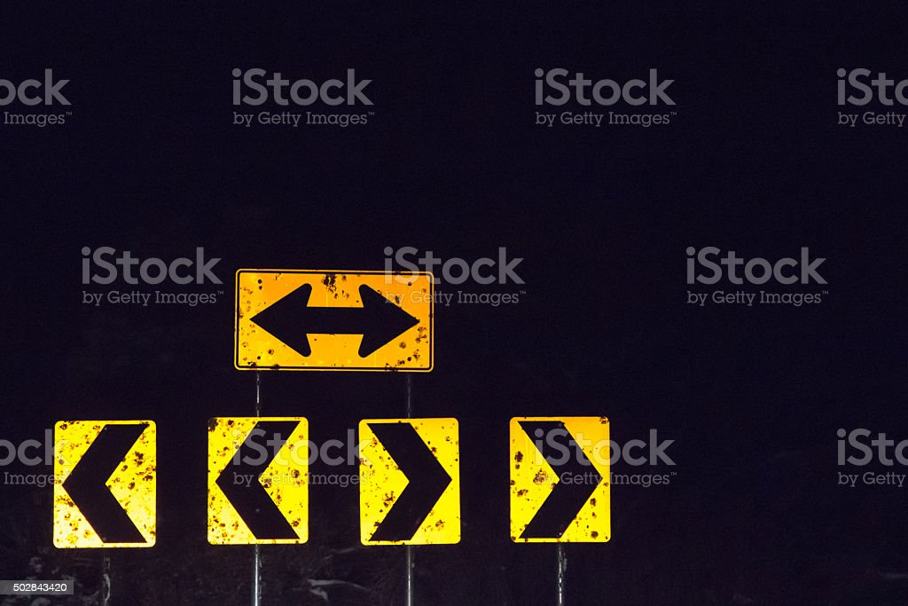 Caution T intersection arrows at night stock photo
