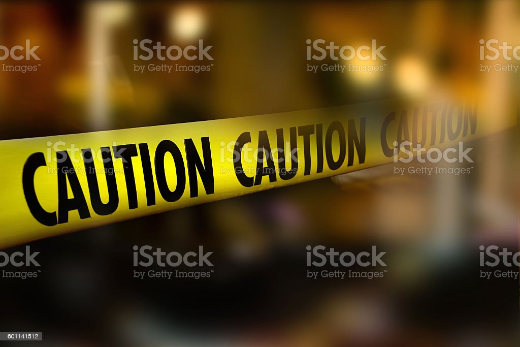 Caution tape and blurred law enforcement and forensic background stock photo