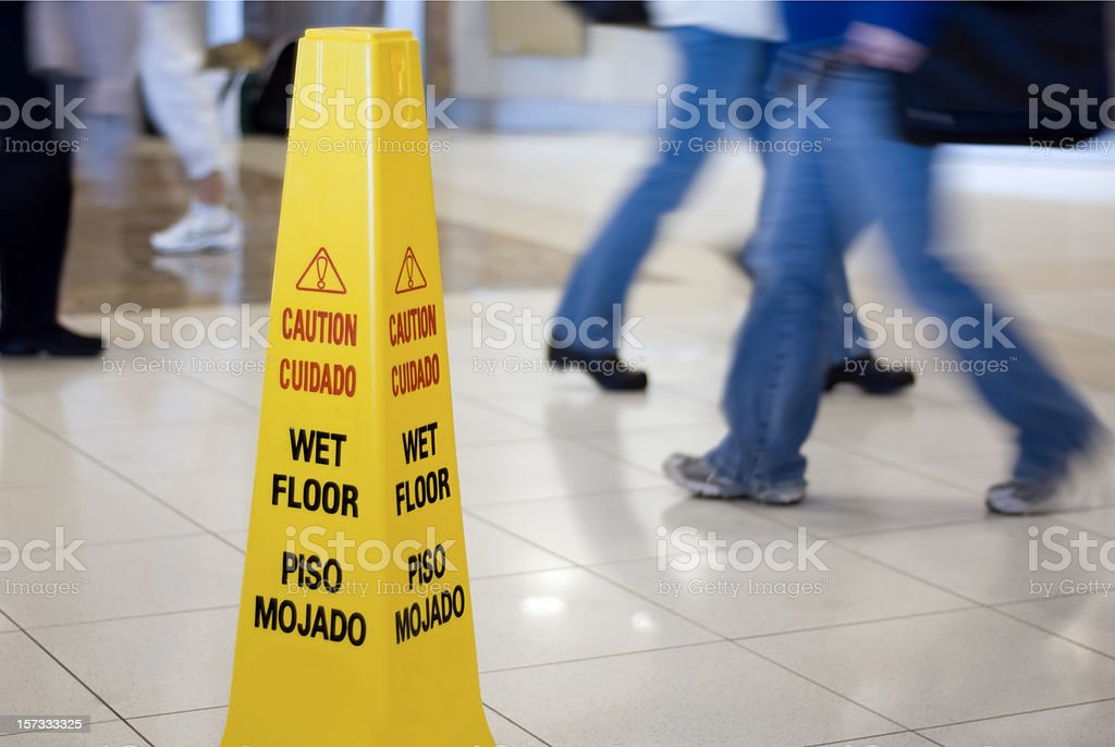 Caution Wet Floor Cone Sign with Motion Blurred Legs Walking stock photo