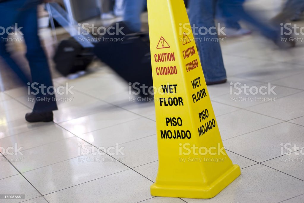 Caution Wet Floor Cone Sign with Motion Blurred People Walking stock photo