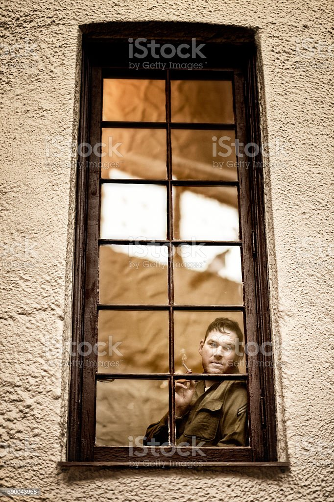 Cautious WWII American Soldier Standing Behind A Window Pane Watching stock photo