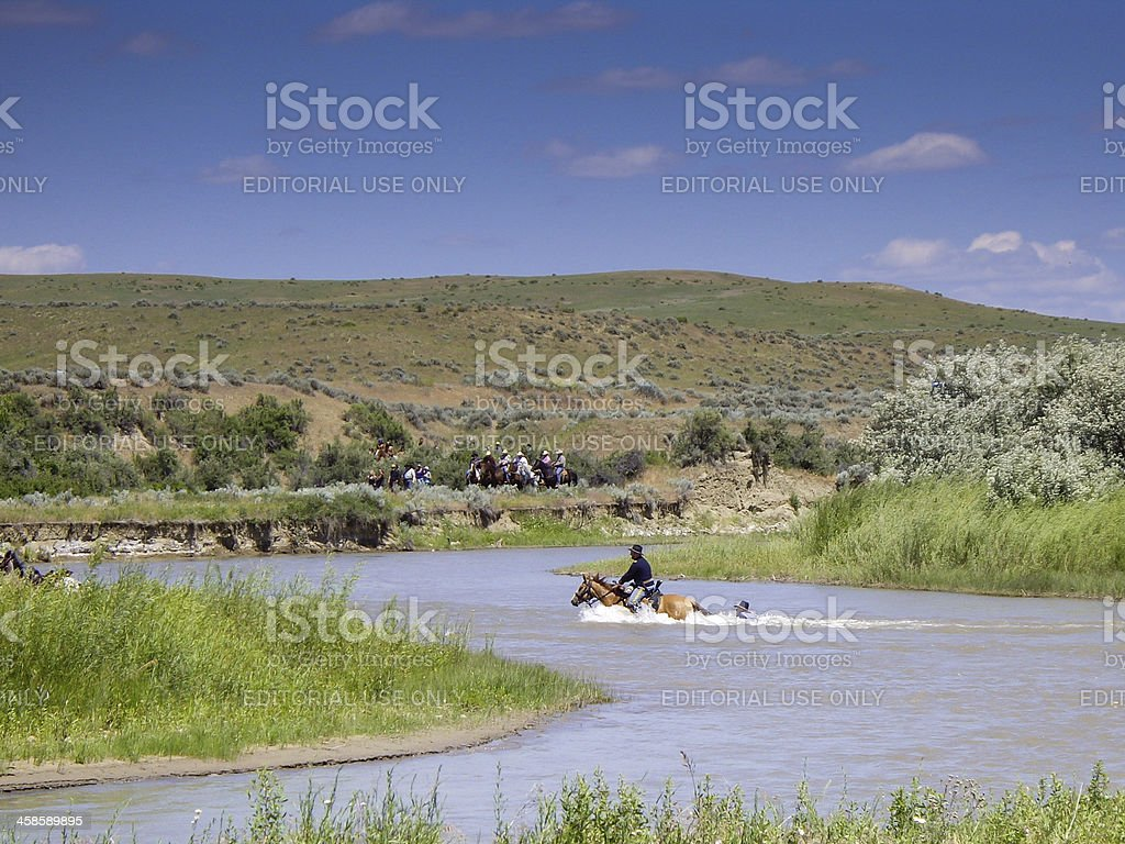 US Cavalry soldier holds on to horses tail in river royalty-free stock photo