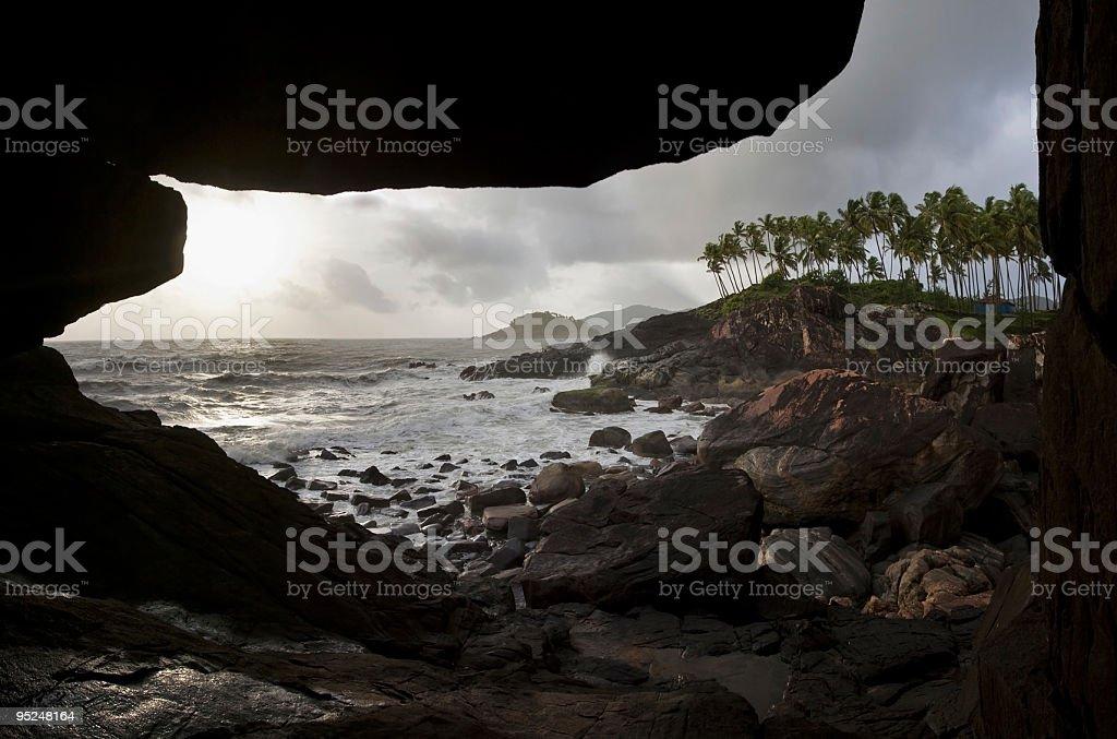 Cave at rocky coastline in Goa stock photo