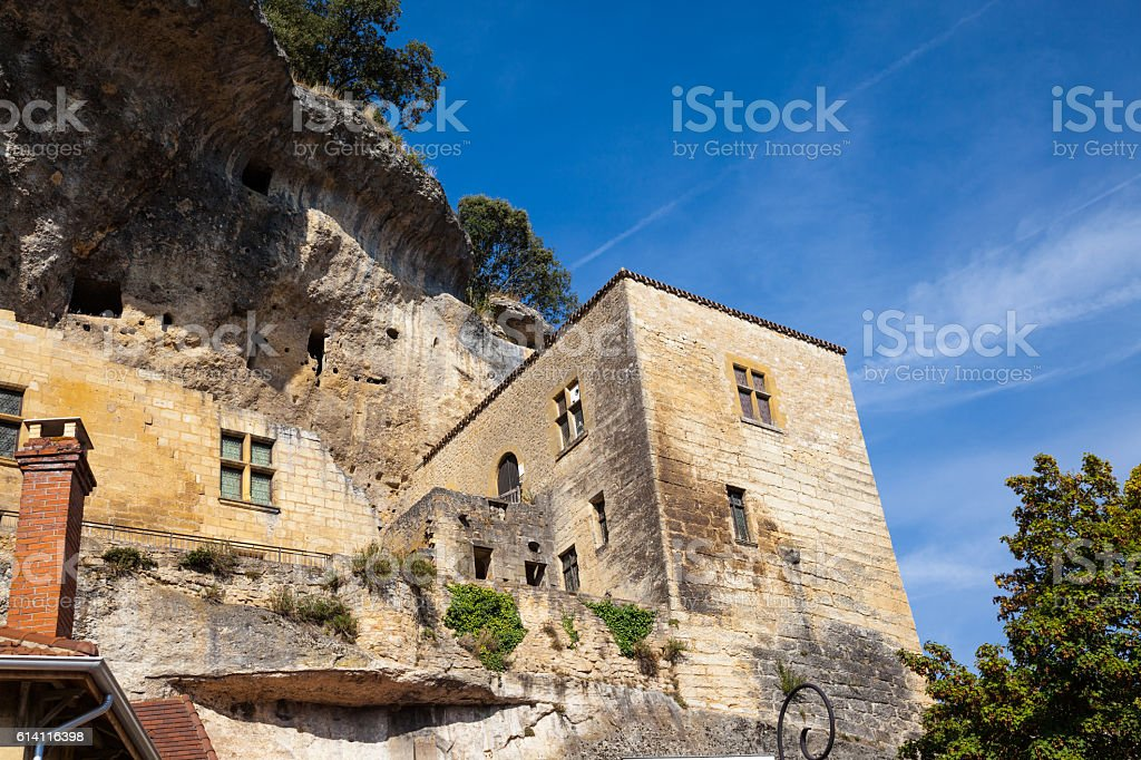 cave dwellings overhanging limestone cliffs in Les Eyzies Dordogne France stock photo