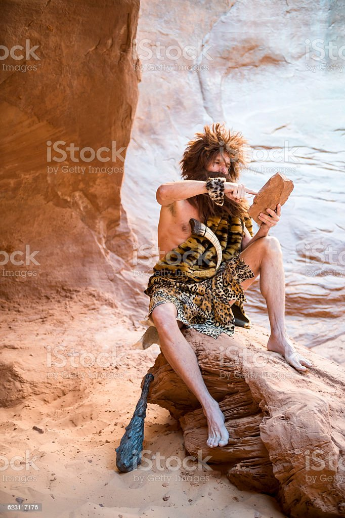 Caveman Sitting Outdoors Using Stone Tablet with Touchscreen stock photo