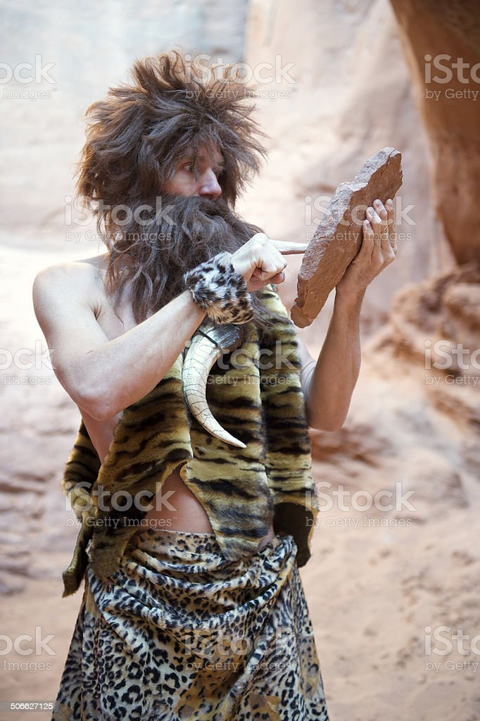 Caveman Standing Outdoors Using Stone Tablet with Touchscreen stock photo