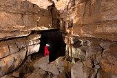 Caver Posing in Beautiful Cave Against Dark Background