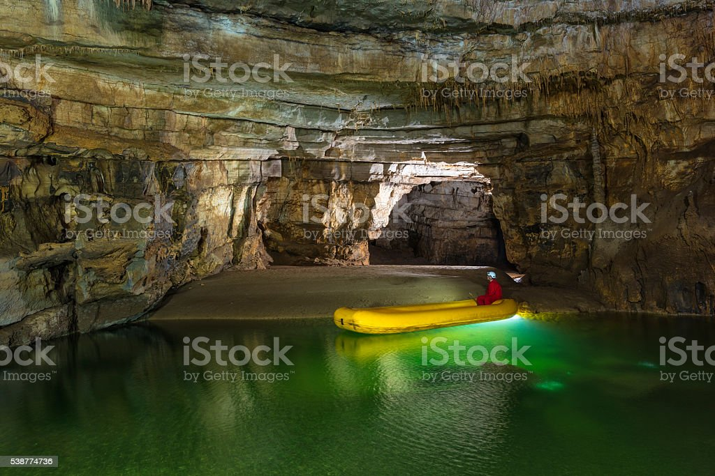 Caver Posing in Beautiful Cave on Yellow Rubber Boat stock photo