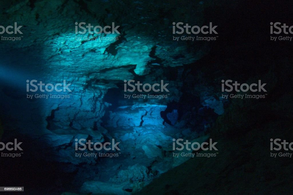 cavern tech sidemount diver going through small entrance in cave cenotes with flashlight viewing halocline salt and fresh water barrier stock photo