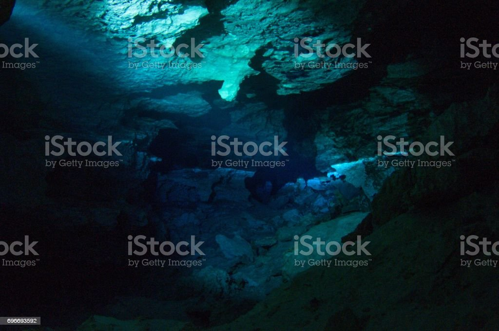 cavern tech sidemount diver going through small entrance in cave cenotes with flashlight viewing halocline salt and fresh water barrier 8 stock photo