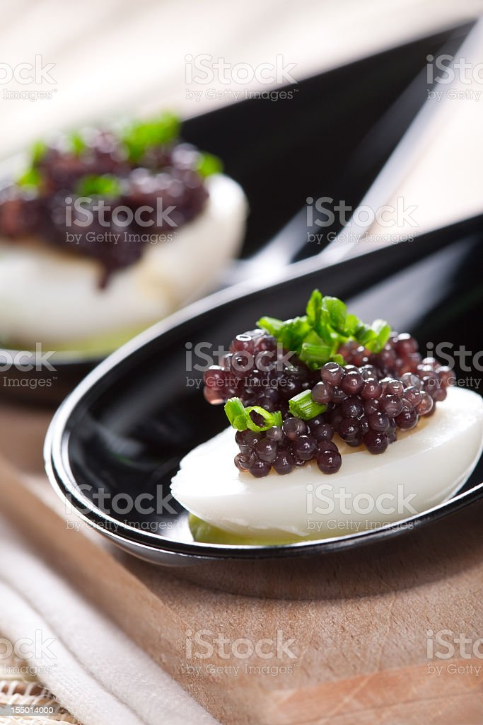 Caviar appetizers on a wooden table stock photo