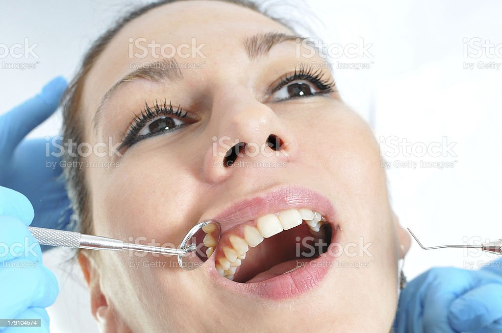 Cavity check up - dentist examining patients mouth and teeth royalty-free stock photo