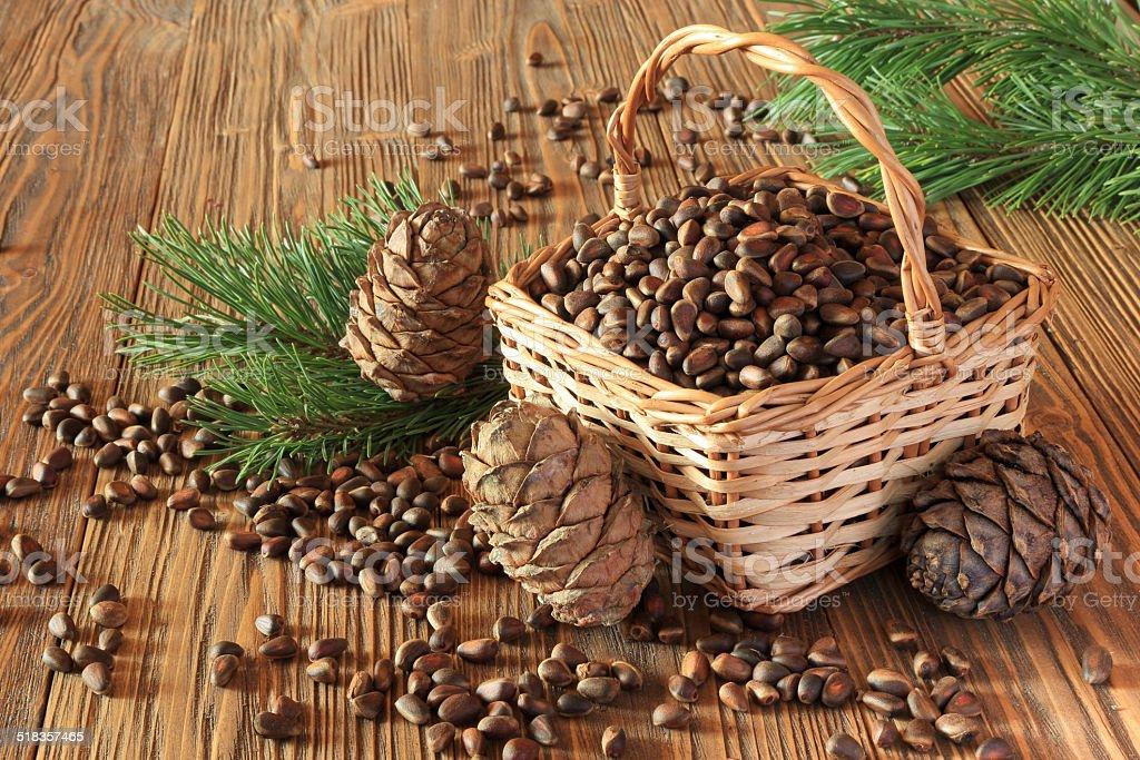 Cedar nuts in  wicker basket on a wooden table stock photo