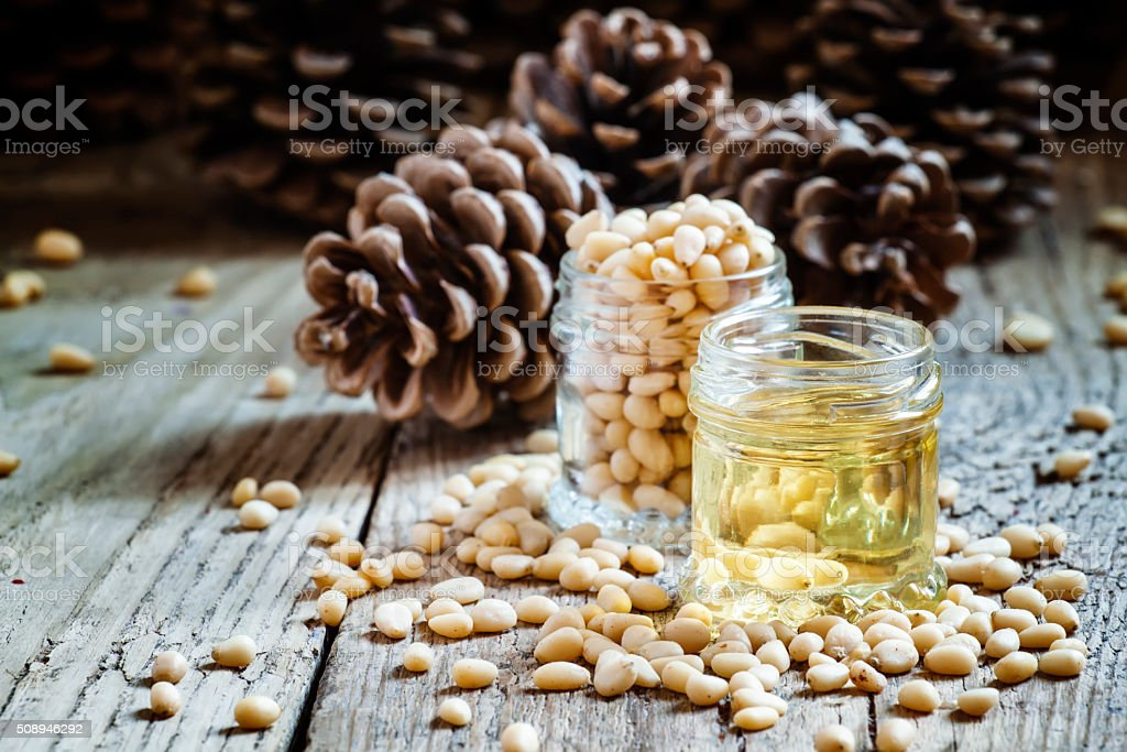 Cedar oil and cedar nuts on an old wooden background stock photo