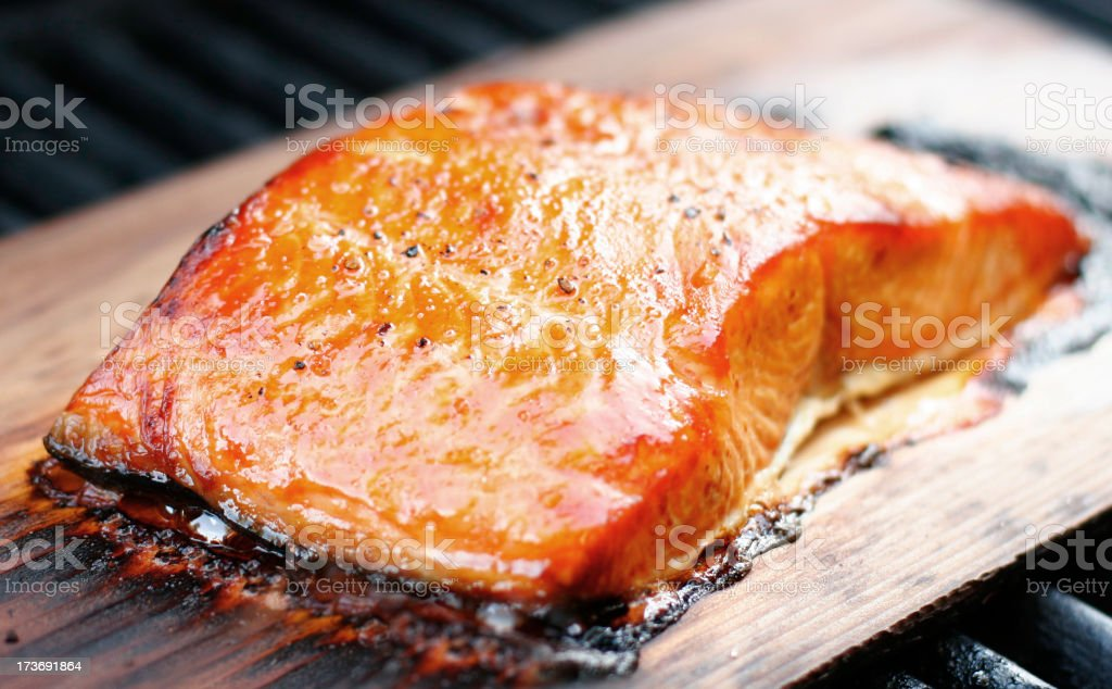 Cedar plank salmon broiling on wooden grill stock photo