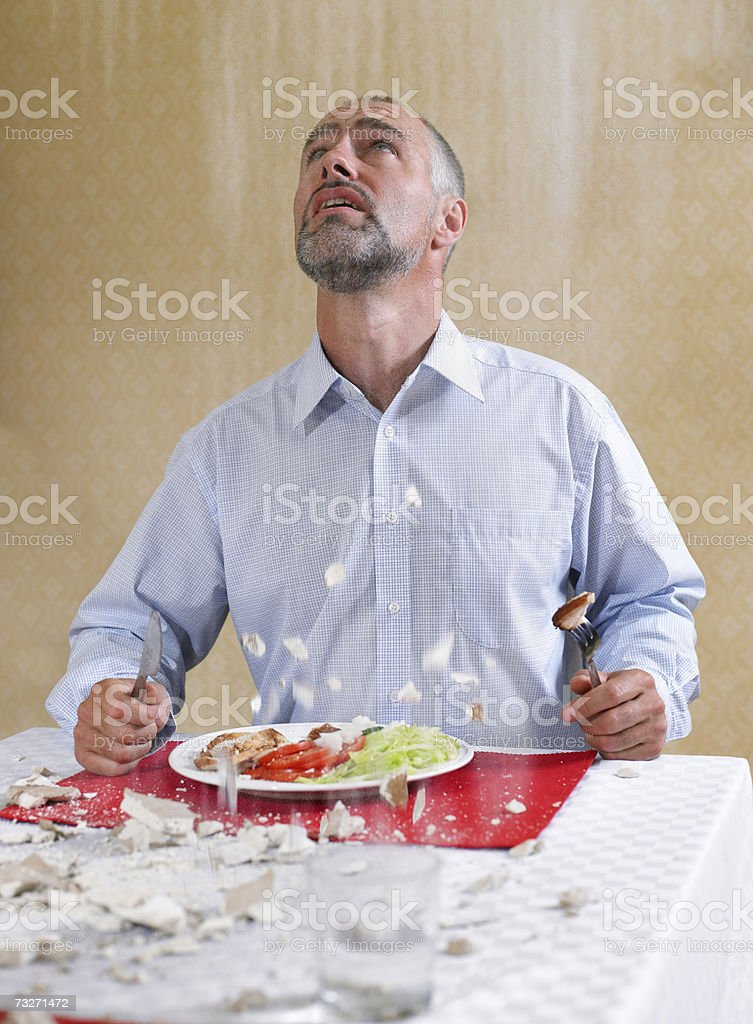 Ceiling falling on man eating meal stock photo
