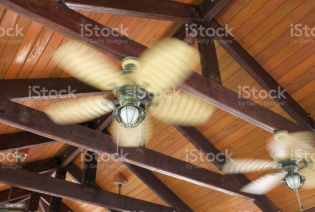 A ceiling fan hooked to a brown wooden plank stock photo