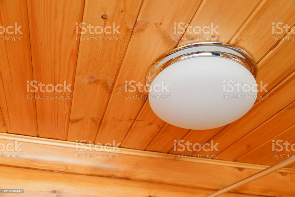 Ceiling glass white lamp on a wooden ceiling stock photo