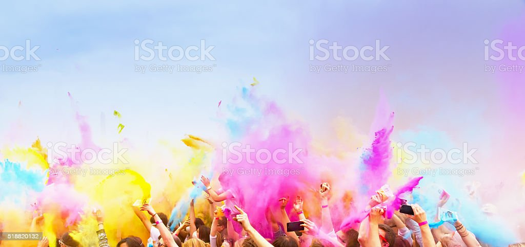 Happy , celebrants with smart phones dancing during the color Holi...