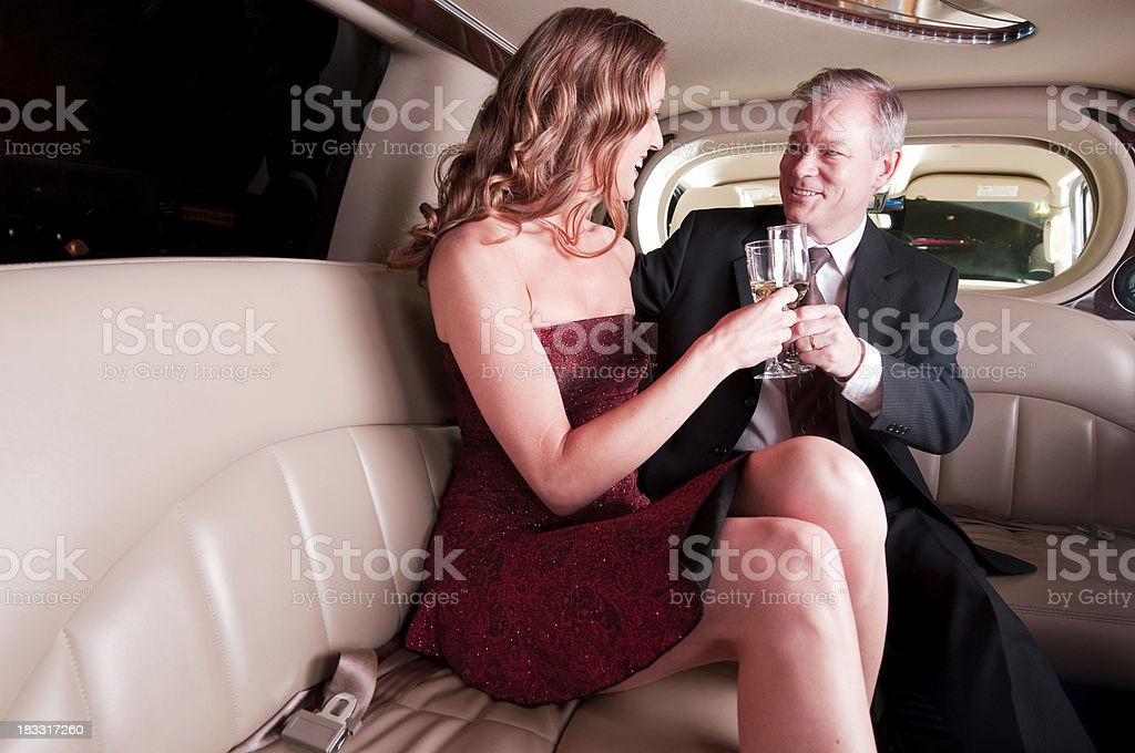 Celebrating couple in limo with champagne glasses stock photo
