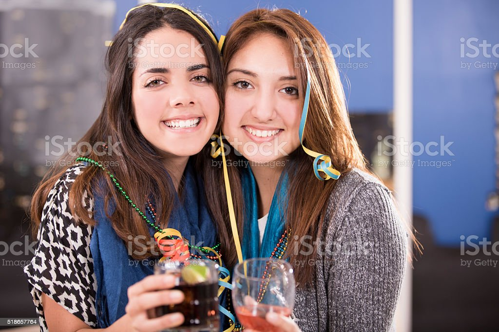 Celebration. Latin descent girl friends pose during party. Drinks. Night. stock photo