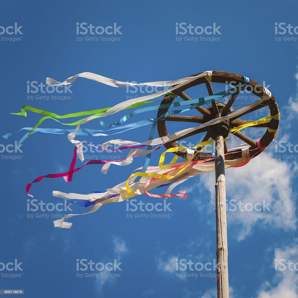 Celebration of Midsummer. Wooden wheel with bright ribbons stock photo