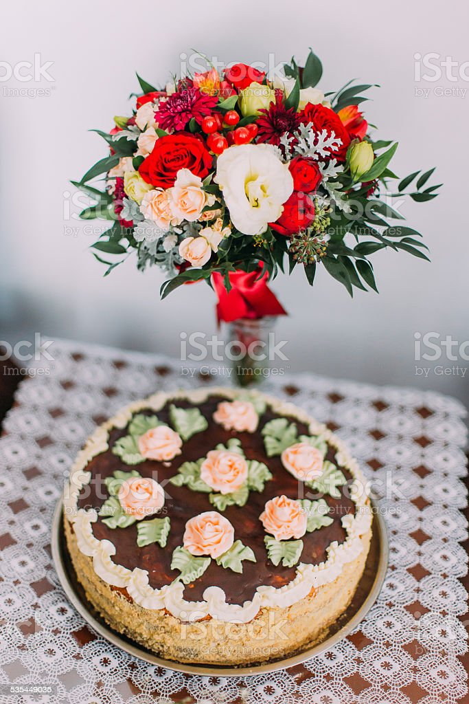 Celebratory homemade chokolate cake decorated with cream roses and red stock photo