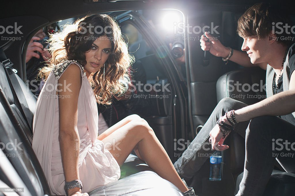 Celebrities emerging from car towards paparazzi stock photo