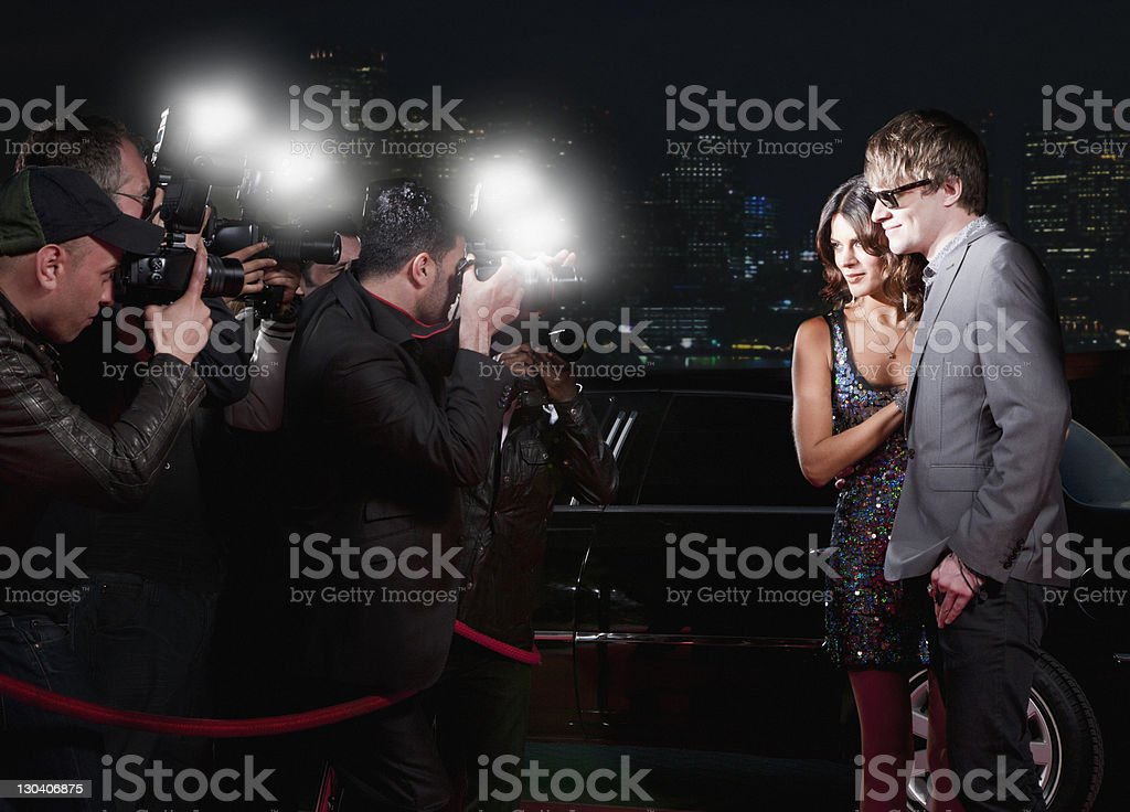 Celebrities posing for paparazzi on red carpet stock photo