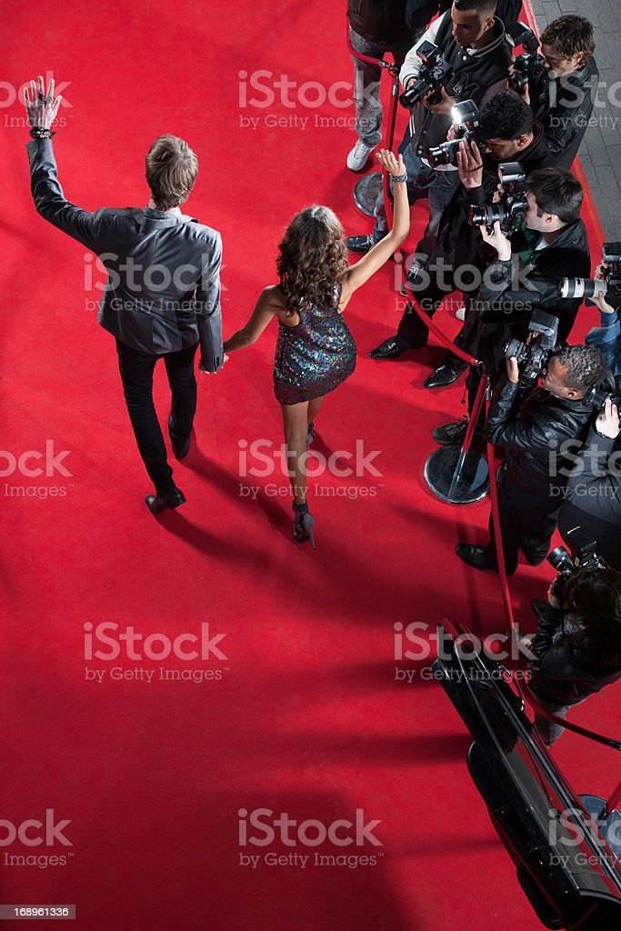 Celebrities waving to paparazzi on red carpet royalty-free stock photo