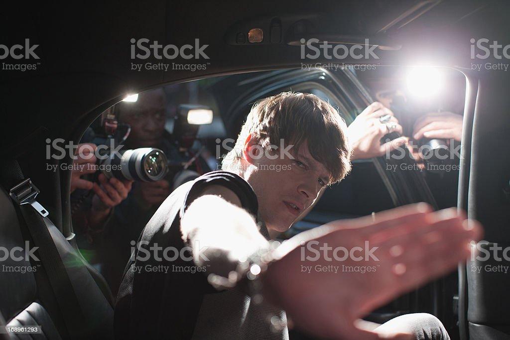 Celebrity blocking photo in backseat of limo stock photo
