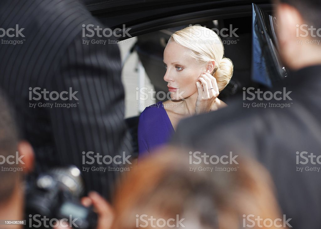 Celebrity emerging from car amid paparazzi royalty-free stock photo