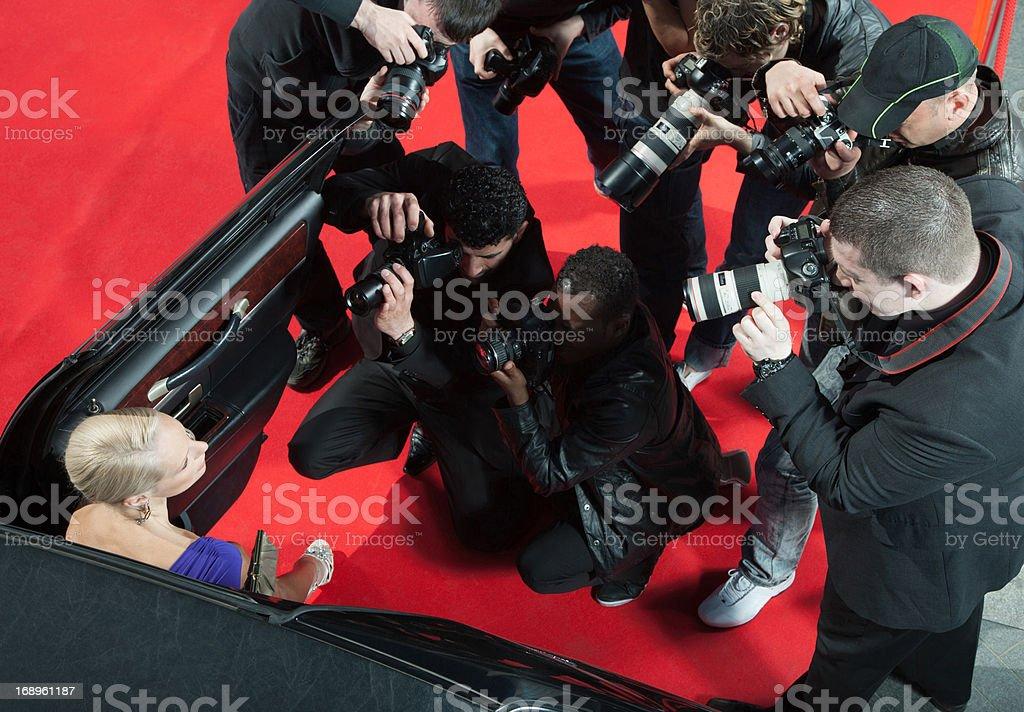 Celebrity emerging from car towards paparazzi stock photo