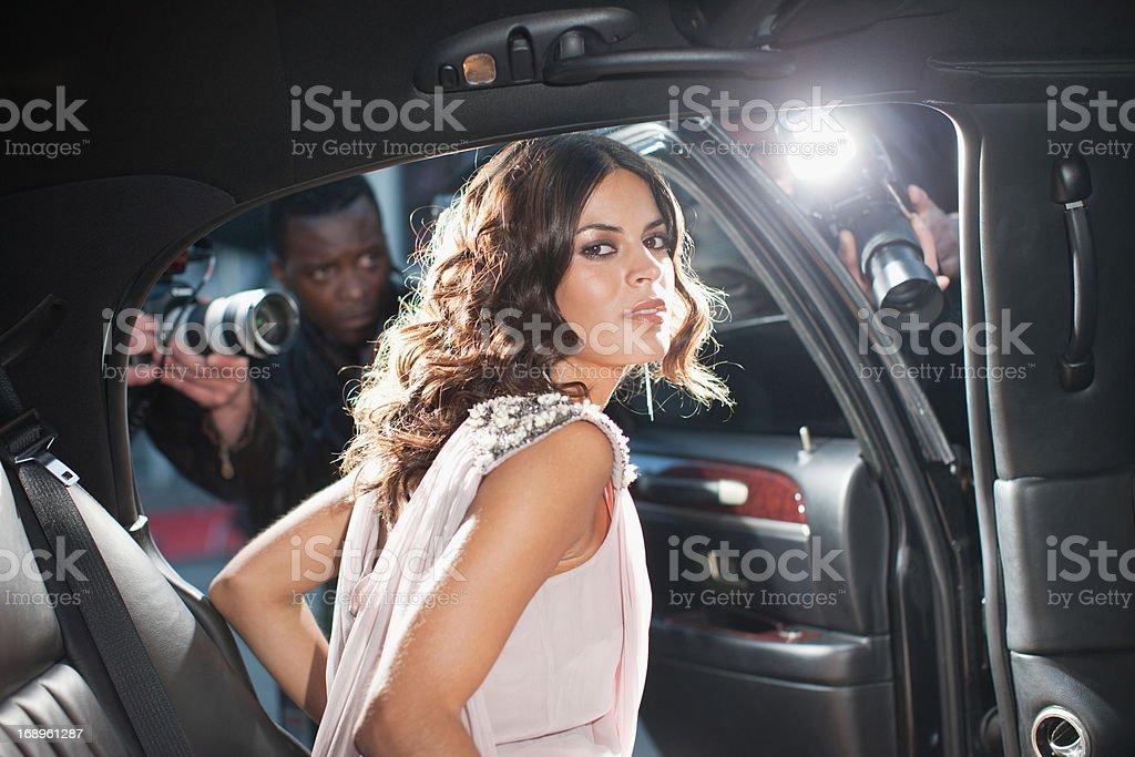 Celebrity emerging from car towards paparazzi royalty-free stock photo