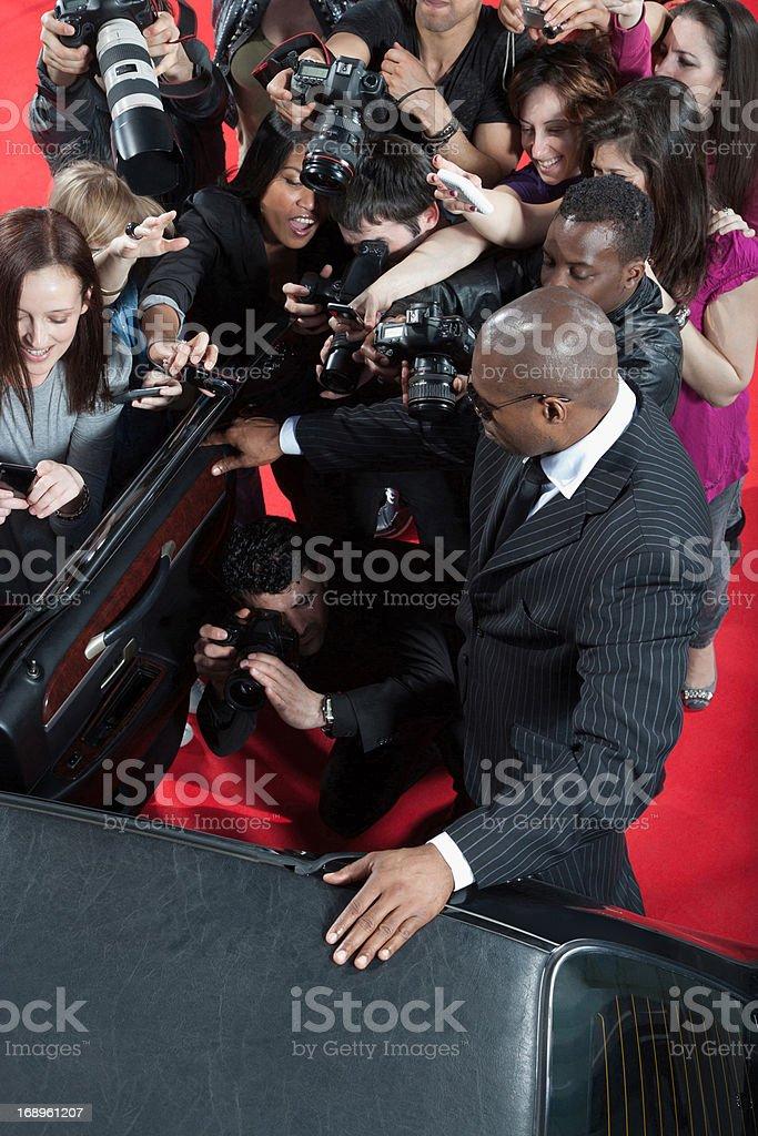 Celebrity emerging from limo toward paparazzi royalty-free stock photo