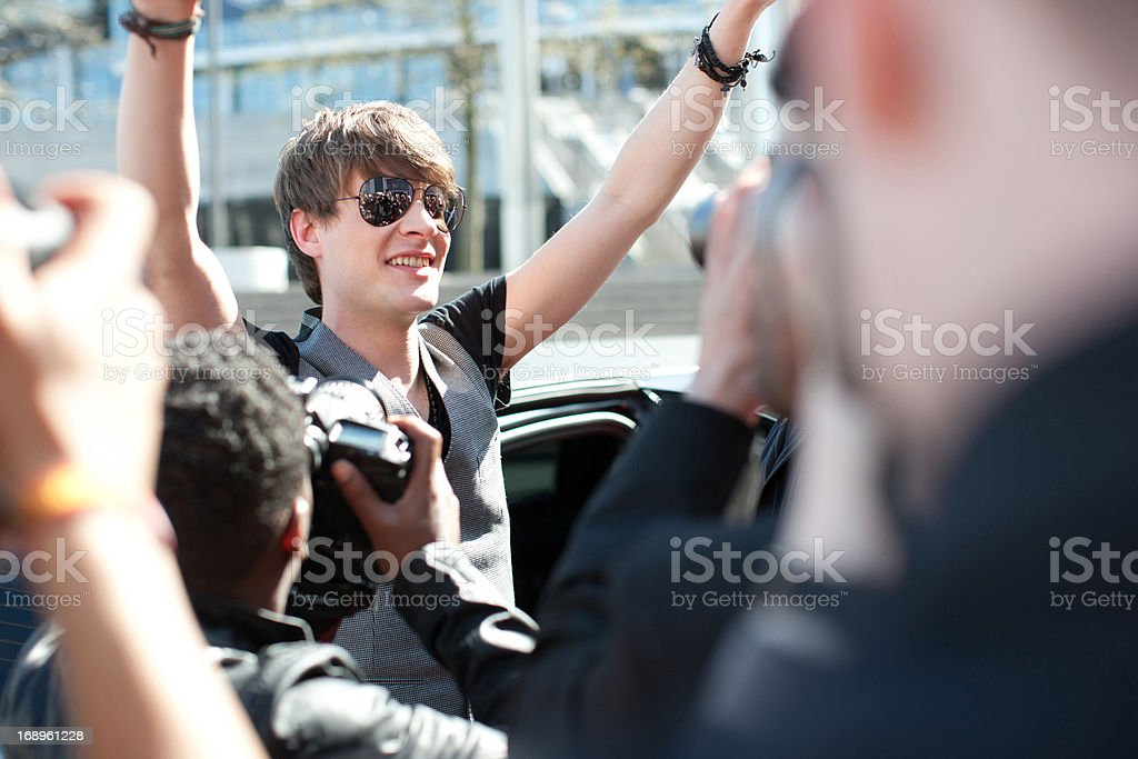 Celebrity emerging from limo towards paparazzi royalty-free stock photo